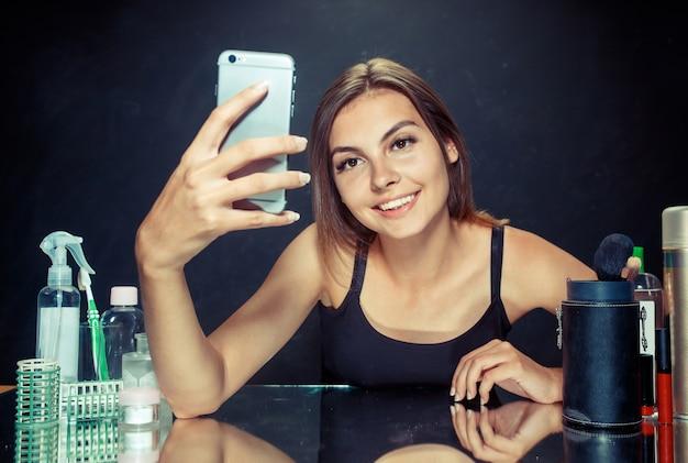 Kobieta uroda po zastosowaniu makijażu. kobieta uroda z makijażem. piękna dziewczyna patrząc na telefon komórkowy i robienie selfie zdjęcie