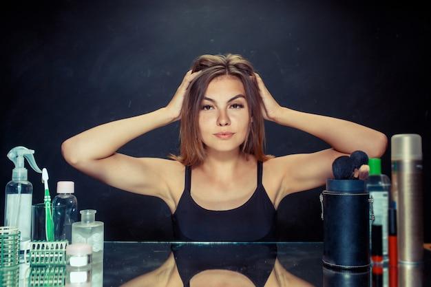 Kobieta uroda po zastosowaniu makijażu. piękna dziewczyna patrzeje w lustrze i stosuje kosmetyka z muśnięciem.