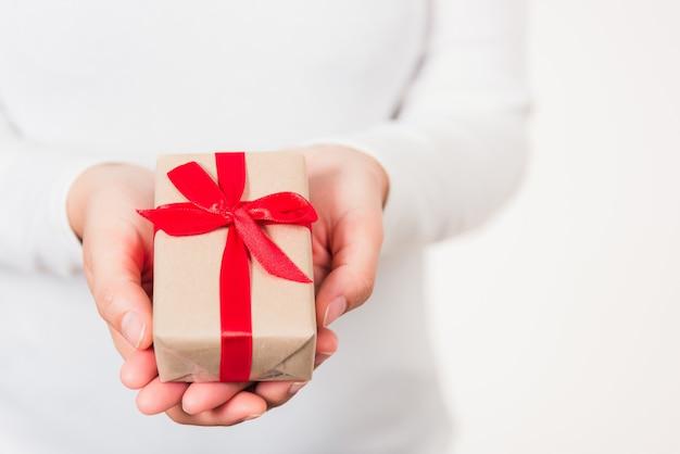 Kobieta uroda ręce trzymając małe pudełko na prezent prezent owinięty papier wstążką