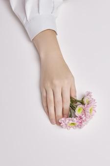 Kobieta uroda ręce z różowe kwiaty w dłoniach na stole. naturalny kosmetyk do pielęgnacji skóry dłoni