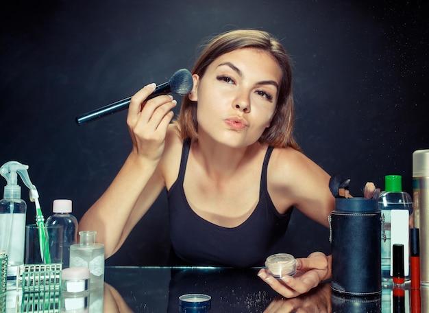 Kobieta uroda stosowania makijażu. piękna dziewczyna patrząc w lustro i nakładając kosmetyk dużym pędzelkiem. model kaukaski w studio