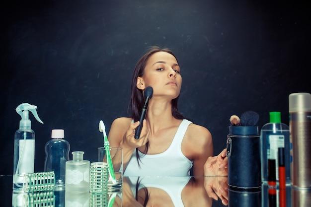 Kobieta uroda stosowania makijażu. piękna dziewczyna patrząc w lustro i nakładając kosmetyk dużym pędzelkiem. rano, makijaż i koncepcja ludzkich emocji. model kaukaski w studio