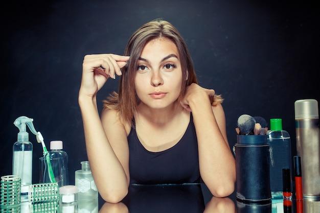 Kobieta uroda stosowania makijażu. piękna dziewczyna patrząc w lustro i nakładając kosmetyk dużym pędzelkiem.