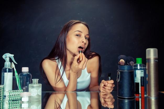 Kobieta uroda stosowania makijażu. piękna dziewczyna patrząc w lustro i nakładając kosmetyk na usta pędzelkiem