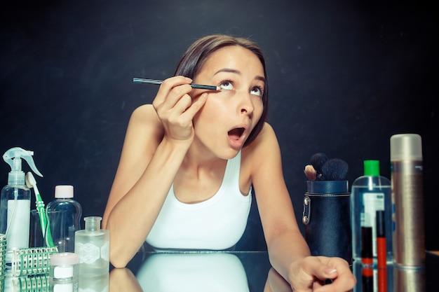 Kobieta uroda stosowania makijażu. piękna dziewczyna patrzeje w lustrze i stosuje kosmetyk z eyeliner.