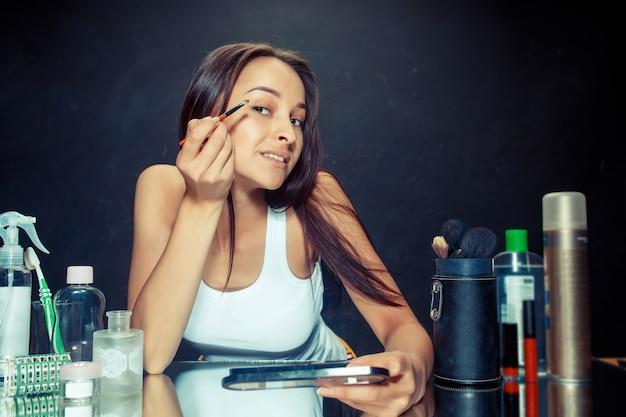 Kobieta uroda stosowania makijażu. piękna dziewczyna patrzeje w lustrze i stosuje kosmetyka z muśnięciem.