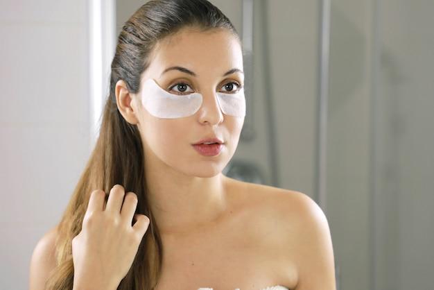 Kobieta uroda twarz z maską pod oczami. piękna kobieta z naturalnym makijażem i łatami z tkaniny na świeżej skórze twarzy.