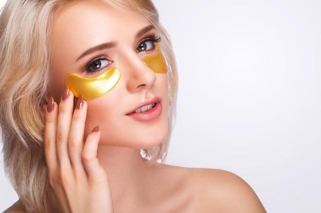 Kobieta uroda twarz z maską pod oczami. piękna kobieta z naturalnym makijażem i złotymi łatami kolagenowymi na świeżej skórze twarzy.