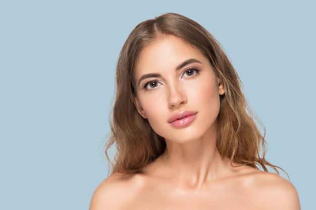 Kobieta uroda twarz zdrowa piękna skóra z bliska portret kobiety na kolor tła. niebieski