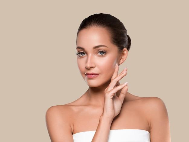 Kobieta uroda zdrowa skóra czyste spa manicure paznokcie ręce dotykając twarzy. kolor tła brązowy