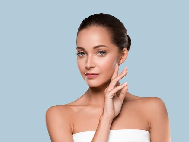 Kobieta uroda zdrowa skóra czyste spa manicure paznokcie ręce dotykając twarzy. kolor tła niebieski