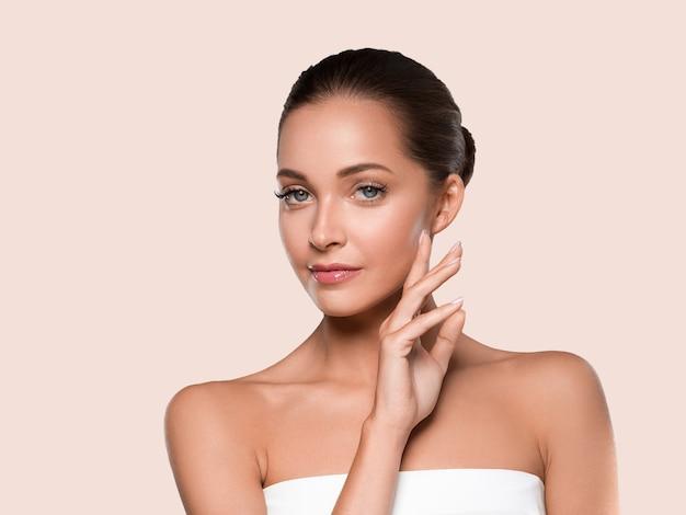 Kobieta uroda zdrowa skóra czyste spa manicure paznokcie ręce dotykając twarzy. kolor tła żółty