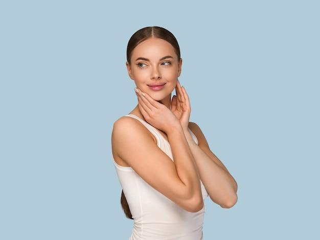 Kobieta uroda zdrowej skóry dotykając twarzy portret studio kosmetyczne. niebieski kolor tła odzieży sportowej