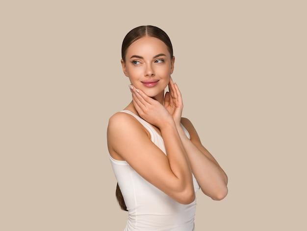Kobieta uroda zdrowej skóry dotykając twarzy portret studio kosmetyczne. odzież sportowa kolor tła brązowy