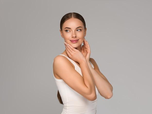 Kobieta uroda zdrowej skóry dotykając twarzy portret studio kosmetyczne. odzież sportowa w kolorze szarym tle