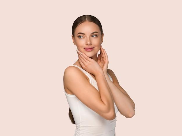 Kobieta uroda zdrowej skóry dotykając twarzy portret studio kosmetyczne. odzież sportowa w kolorze żółtym tle