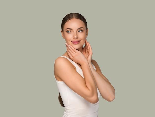Kobieta uroda zdrowej skóry dotykając twarzy portret studio kosmetyczne. zielony kolor tła odzieży sportowej