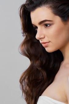 Kobieta uroda zdrowej skóry i fryzury, brunetka z długimi włosami