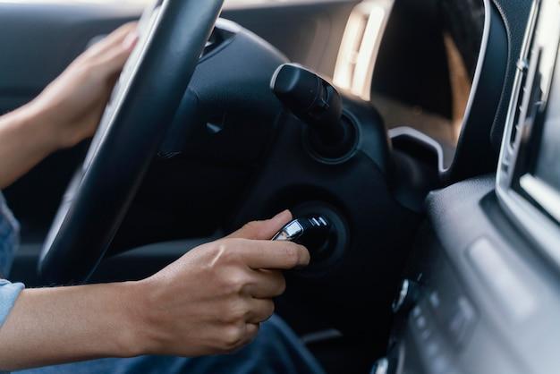 Kobieta uruchamia silnik swojego samochodu