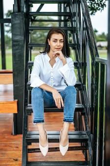 Kobieta usiadła na schodach i spojrzała na przód
