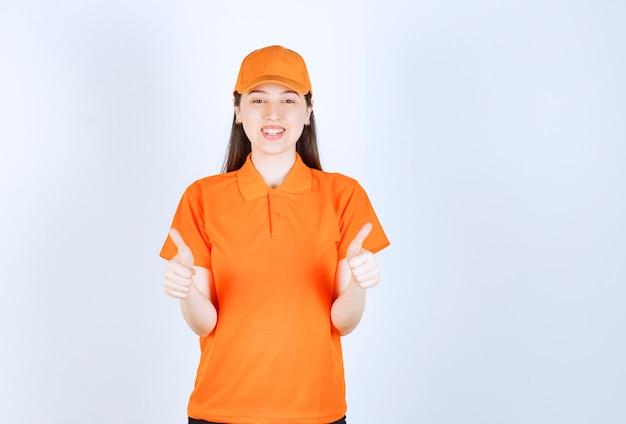 Kobieta usługi agent nosi strój w kolorze pomarańczowym i pokazuje pozytywny znak ręką.