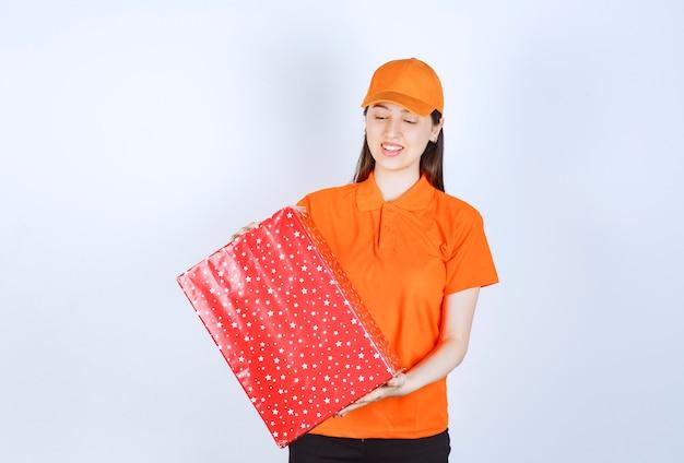 Kobieta usługi agent w dresscode kolor pomarańczowy, trzymając czerwone pudełko.
