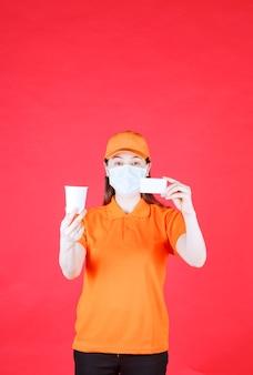 Kobieta usługowa w pomarańczowym mundurze i masce trzyma jednorazowy kubek i prezentuje swoją wizytówkę.