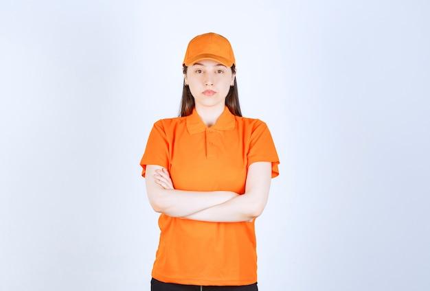 Kobieta usługowa w pomarańczowym mundurze, skrzyżowana ramiona i wygląda profesjonalnie.