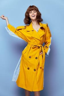 Kobieta uśmiech gest z ręką żółty płaszcz jasny makijaż styl życia