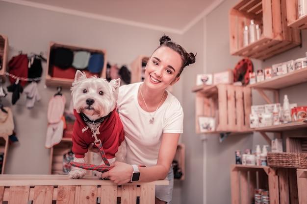 Kobieta uśmiecha się. ciemnowłosa atrakcyjna młoda kobieta uśmiecha się po założeniu czerwonego ubrania na psa