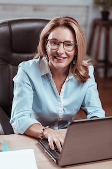 Kobieta uśmiecha się. dojrzała bizneswoman ubrana w stylową bluzkę uśmiechnięta przed rozpoczęciem nowego ekscytującego projektu