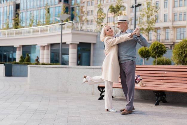 Kobieta uśmiecha się. dwóch emerytów tańczy w parku.