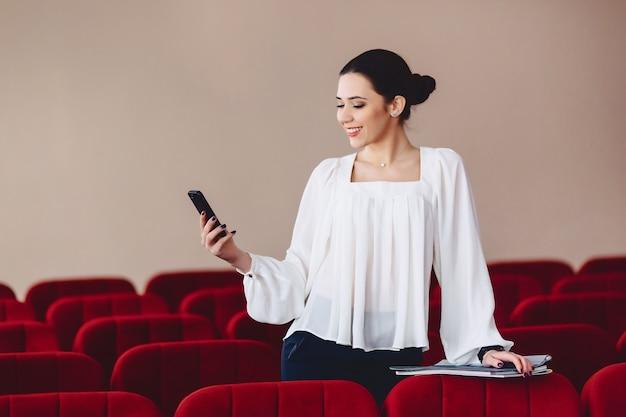 Kobieta uśmiecha się i pisze sms na telefon