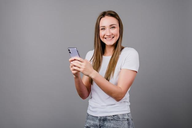 Kobieta uśmiecha się i przewija ekran telefonu na szarym tle