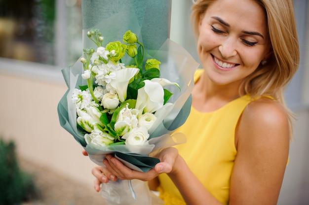 Kobieta uśmiecha się i trzyma bukiet kalii, piwonii i róż
