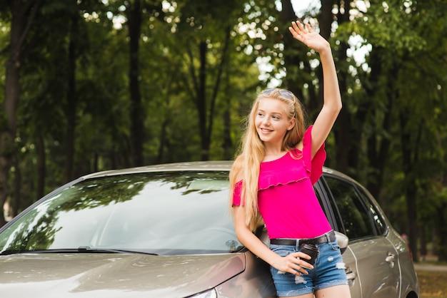 Kobieta uśmiecha się i wita ręką w pobliżu samochodu