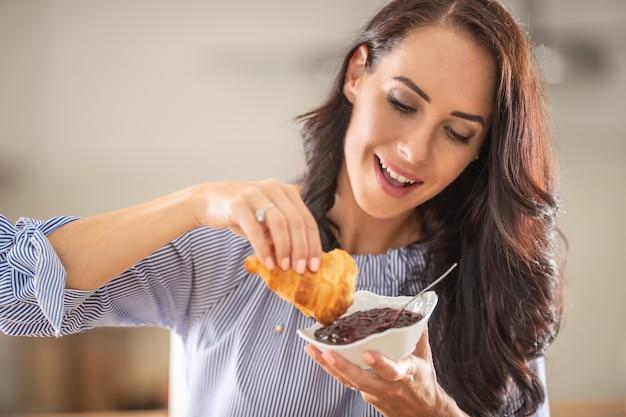 Kobieta uśmiecha się, jedząc śniadanie z rogalikiem i dżemem.