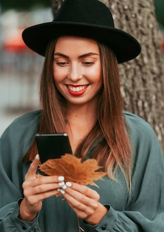 Kobieta uśmiecha się, patrząc na swój telefon
