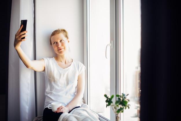 Kobieta uśmiecha się podczas rozmowy, patrząc na smartfona w pomieszczeniu.