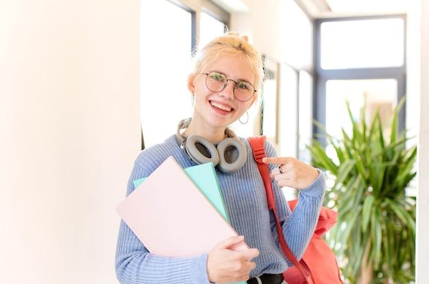 Kobieta uśmiecha się radośnie, czuje się szczęśliwa i wskazuje na bok i do góry, pokazując obiekt w przestrzeni kopii