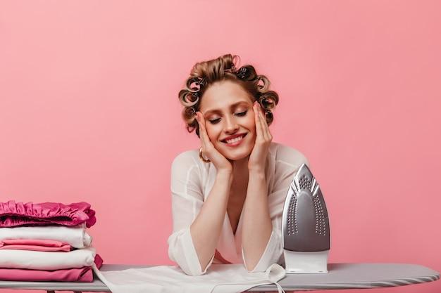 Kobieta uśmiecha się radośnie, prasując wszystkie swoje ubrania