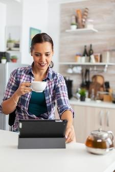 Kobieta uśmiecha się rano przy użyciu komputera typu tablet i delektuje się filiżanką gorącej zielonej herbaty