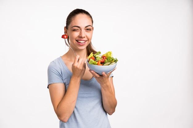 Kobieta uśmiecha się sałatki i trzyma