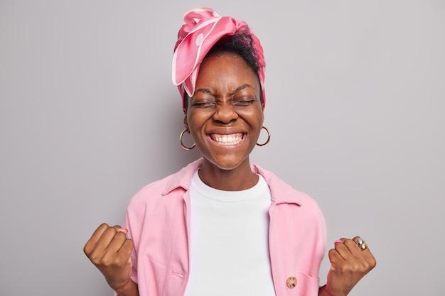 Kobieta uśmiecha się szeroko białe zęby zaciska pięści korzenie zespołu oczekuje wyników ubrana w modne ciuchy odizolowane na szaro