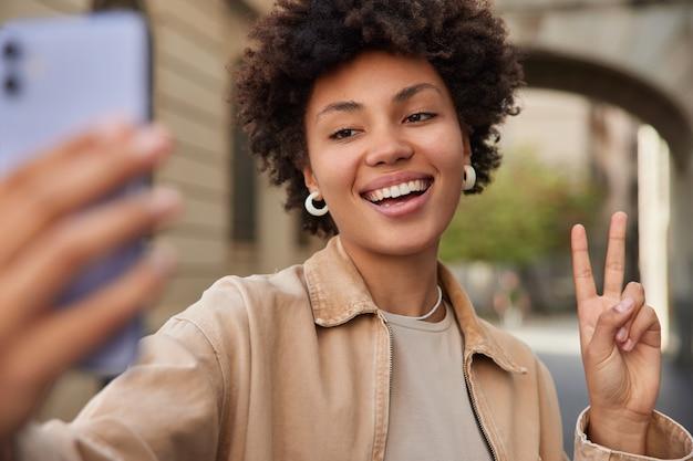 Kobieta uśmiecha się szeroko robi sefie portret pokazuje znak pokoju uśmiecha się szeroko spaceruje po mieście ubrana w stylowe ubrania lubi wolny czas w miejskim otoczeniu