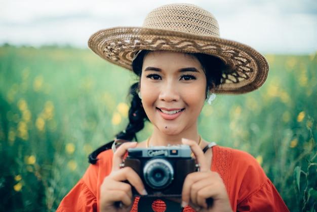 Kobieta uśmiecha się trzymając aparat fotograficzny