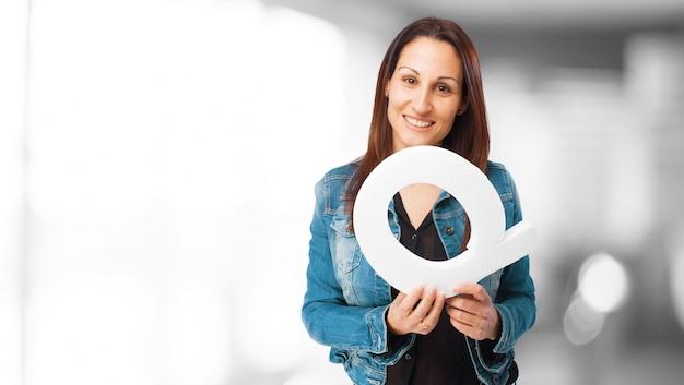 Kobieta uśmiecha się trzymając literę