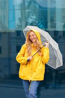 Kobieta uśmiecha się w żółtym płaszczu przeciwdeszczowym z parasolem na niebieskim tle w mieście