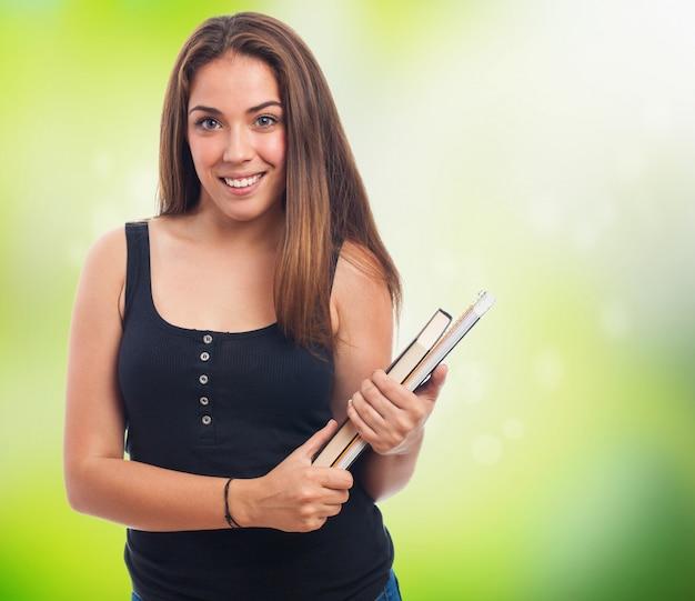 Kobieta uśmiecha się z książek i zeszytów w rękach
