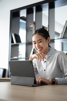 Kobieta uśmiechając się i oglądając seminarium internetowe na tablecie w biurze.